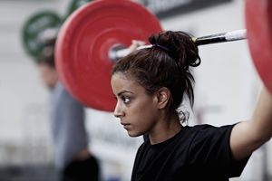Young woman lifting weight