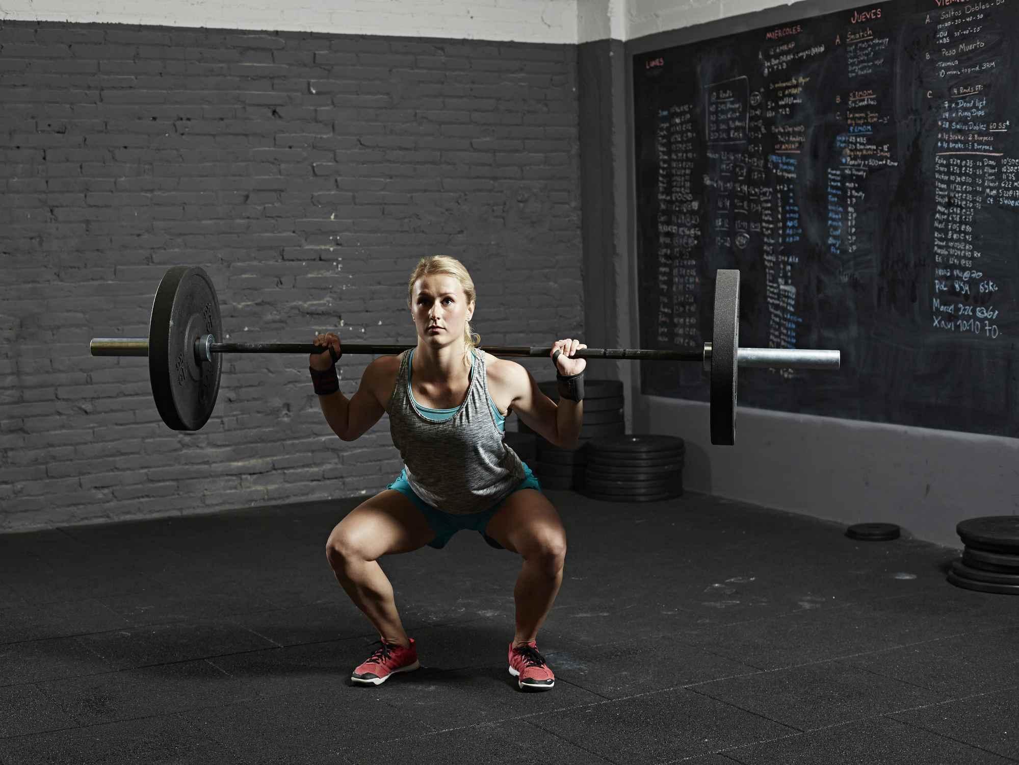 Female gym performing back squat