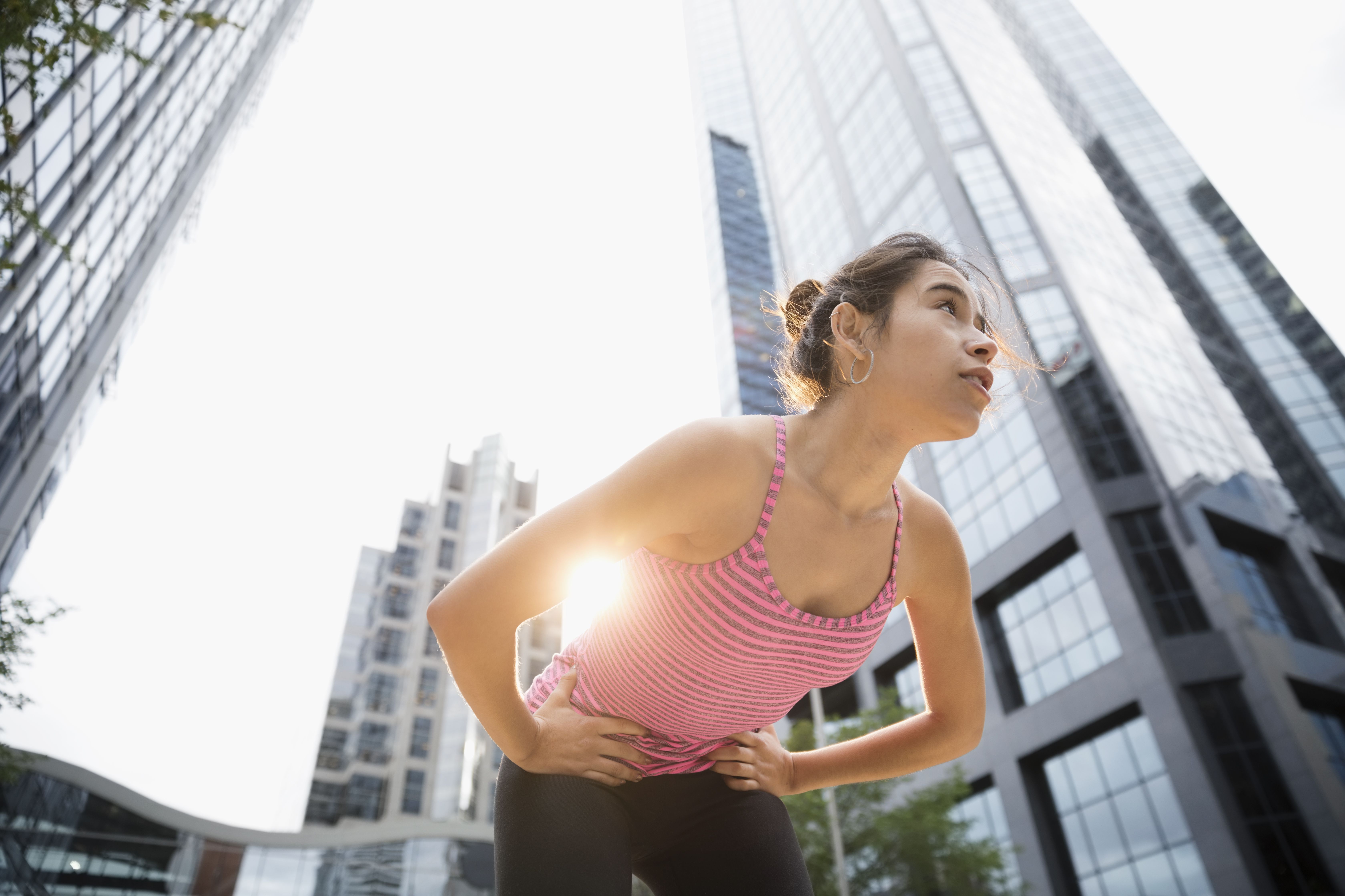Tired young female runner resting, bending below urban highrise building