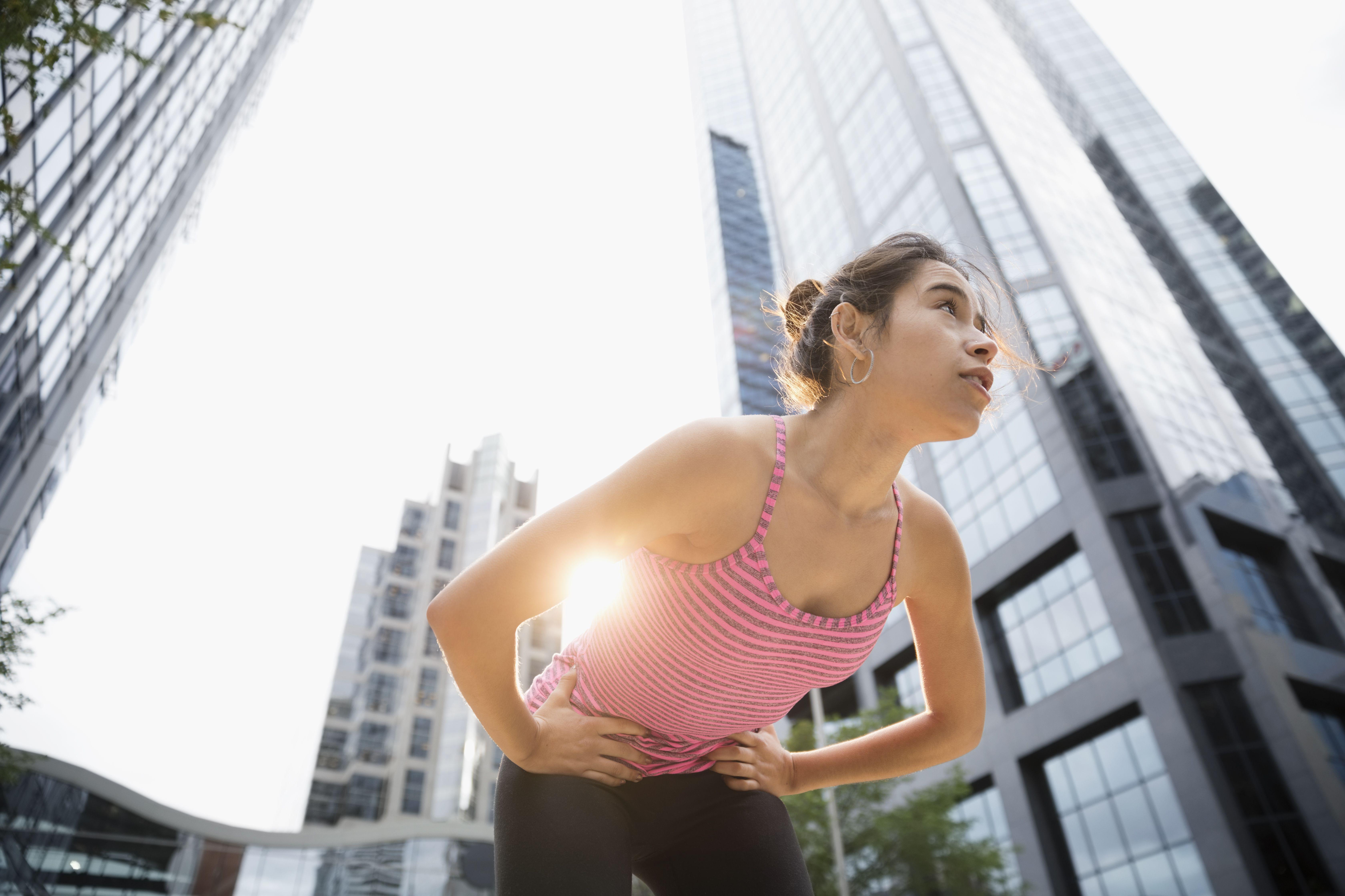 Corredor de sexo femenino joven cansado descansando, doblando debajo del edificio de gran altura urbano