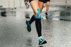 Woman runs in rain with blue kinesiology tape applied to knee