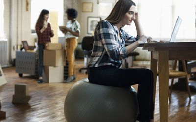 woman sitting on exercise ball while working on a computer