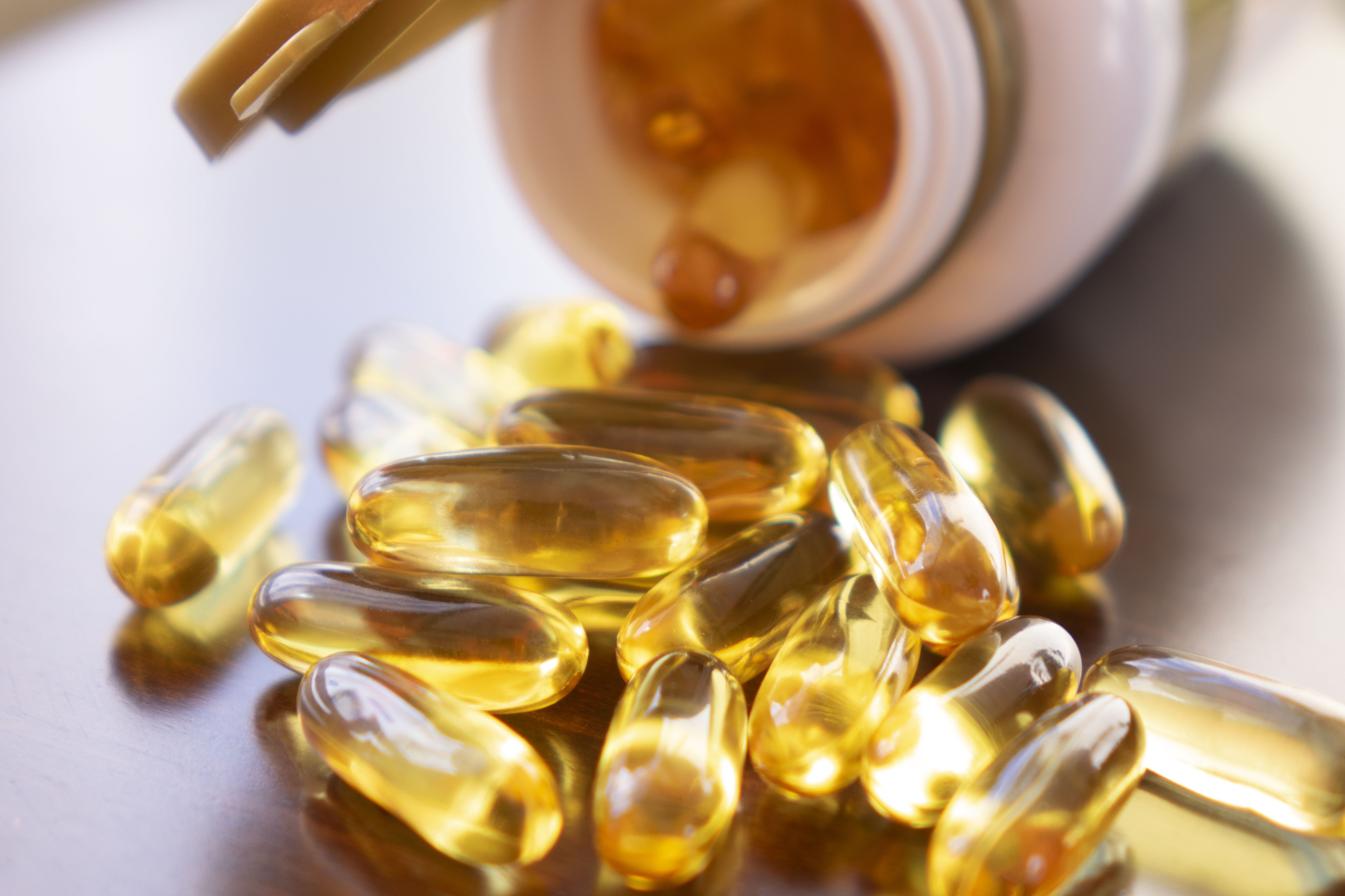 Fish oil capsules with omega 3 and vitamin D in a glass bottle on wooden texture, healthy diet concept, close up shot.