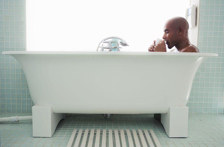 Man drinking coffee in a bath tub