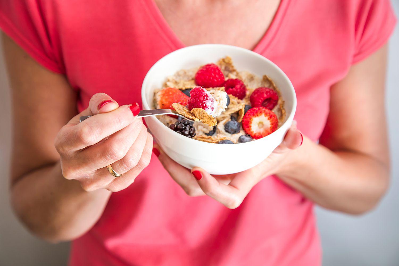 Cosecha de primer plano de mujer sosteniendo un cuenco que contiene granola casera o muesli con copos de avena, copos de maíz, frutos secos con bayas frescas.  Desayuno saludable