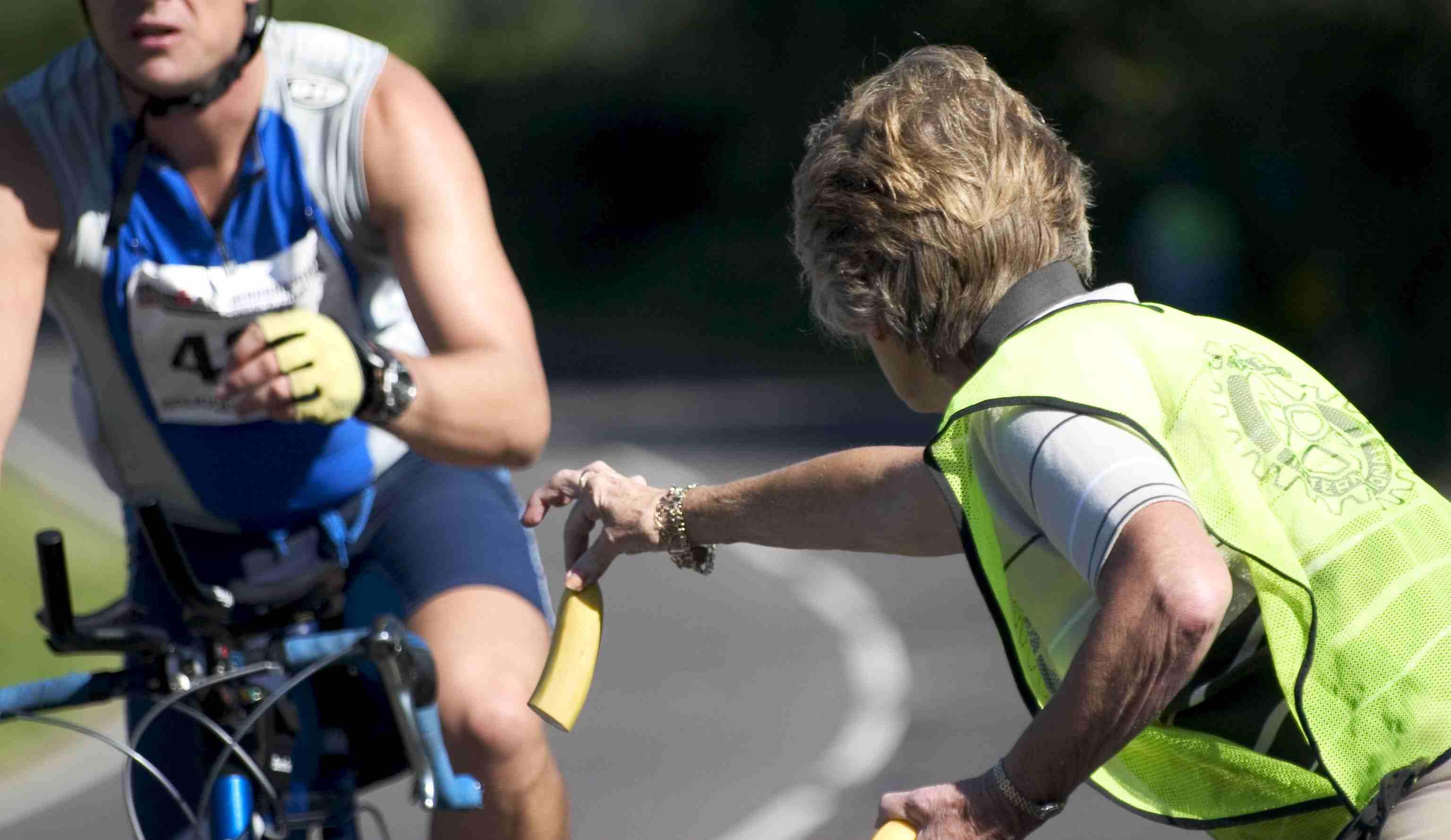 Man handing banana to biker during race