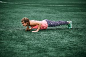 A woman performs a burpee in a grassy field.