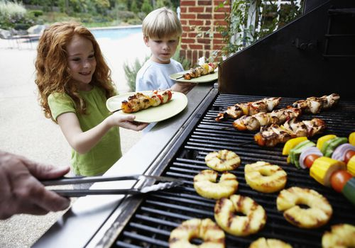 Boy and girl holding up plates next to grill cooking vegetables and pineapple