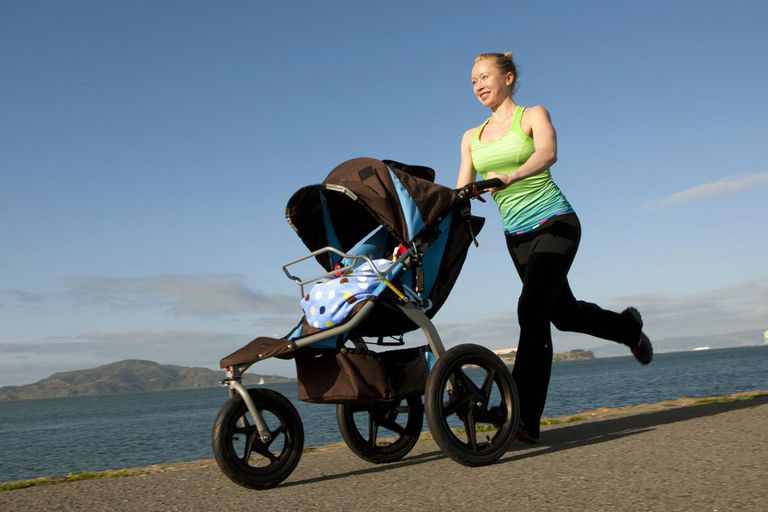 Woman in fitness clothes running with baby jogger.