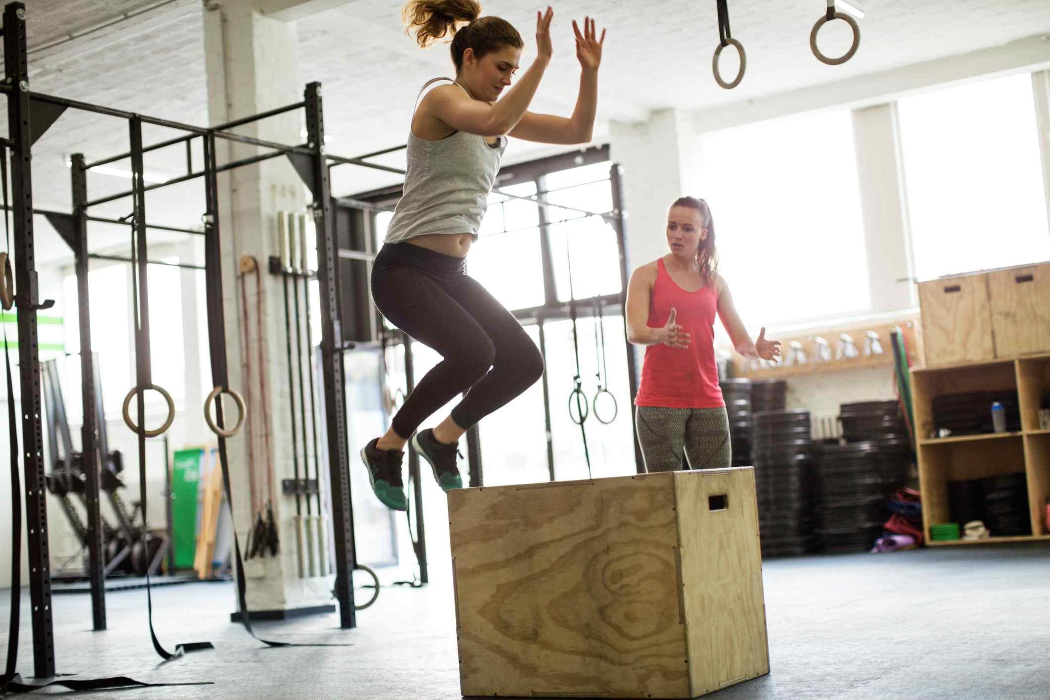 Mujer haciendo salto de caja pliométrica en el gimnasio