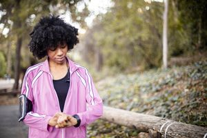 Woman looking at fitness tracker while walking outside