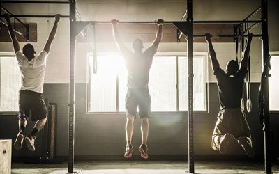 Three male CrossFit athletes do pull-ups in a CrossFit gym.