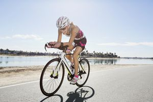 female cyclist riding bike on road near lake