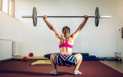 A CrossFit athlete in a pink sports bra and workout shorts, facing away from camera, performs an overhead squat in a small gym.