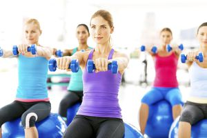 Young female friends exercising with dumbbells while sitting on pilates balls in gym class. Horizontal shot.