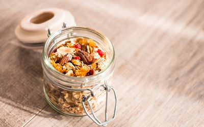 Homemade muesli with oat flakes, dried fruits and nuts in a jar, selective focus