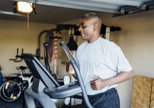 Black man running on treadmill in garage