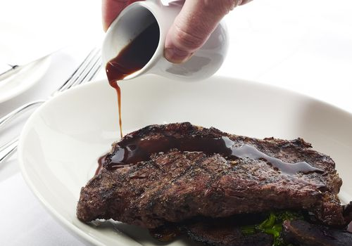worcestershire sauce poured on steak