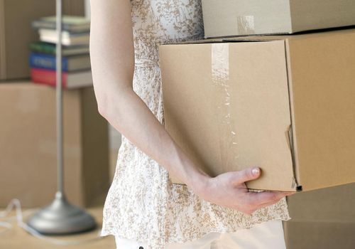Woman carrying stack of moving boxes
