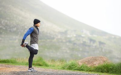 Man stretching during a run in the mountains
