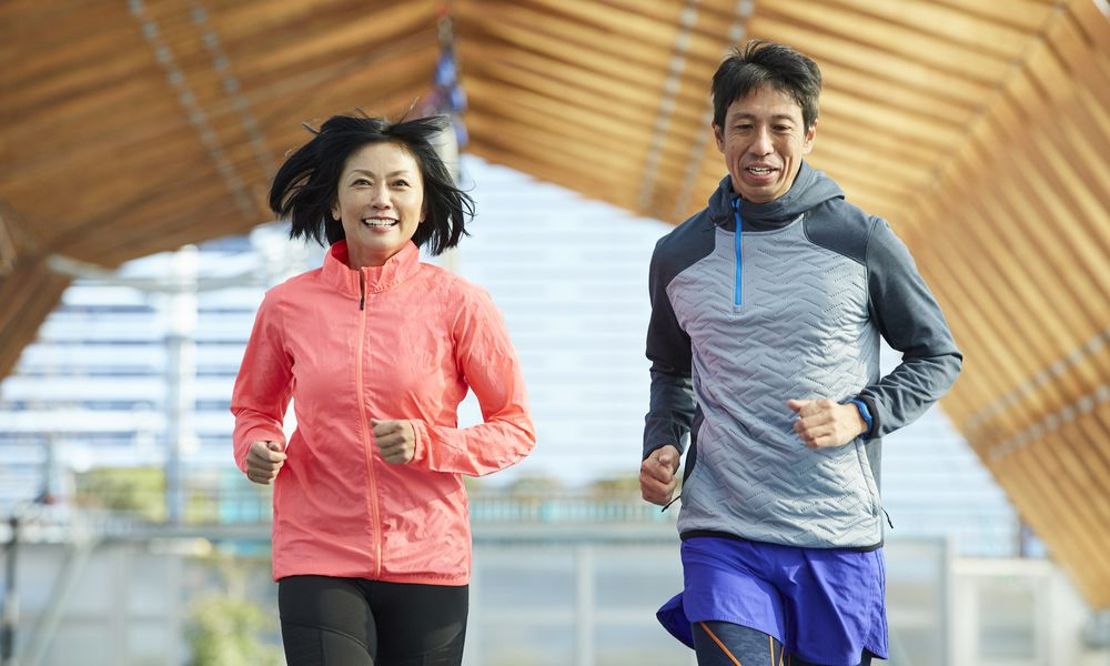 Mature Japanese sportsman and sportswoman running on track