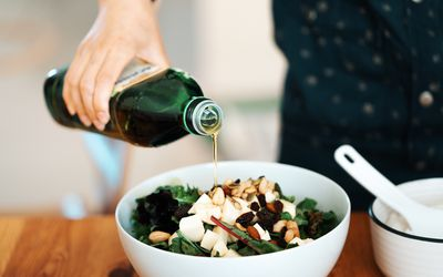 Fresh green salad with olive oil, mozzarella, mixed nuts, and dry fruits