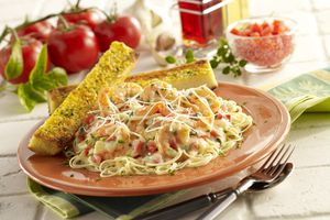 Shrimp pasta with garlic bread on counter with tomatoes in background.