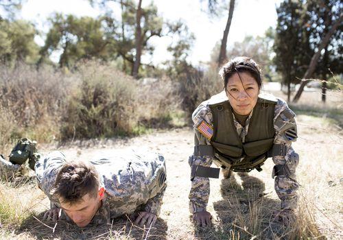 Ejército mujer y hombre haciendo flexiones en campo