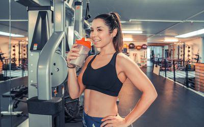 Attractive young woman drinking protein shake at gym