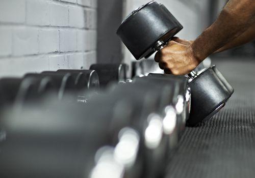 Hombre atlético levantando pesas en el gimnasio