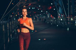 Young Woman Jogging At Night on the bridge
