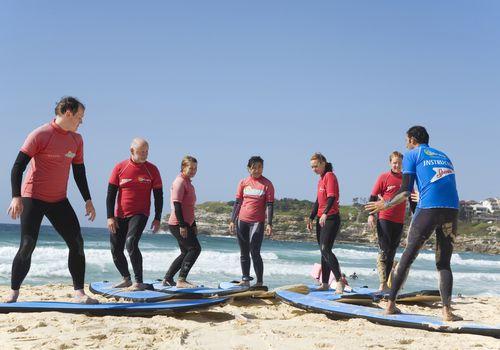 adultos en clase de surf