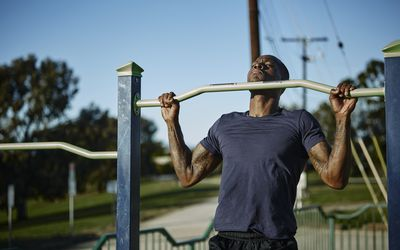 A man does pull-ups on a pull-up bar outdoors in a gated park
