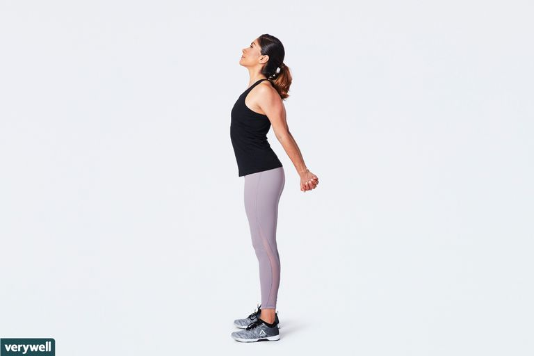 woman doing standing chest opener stretch