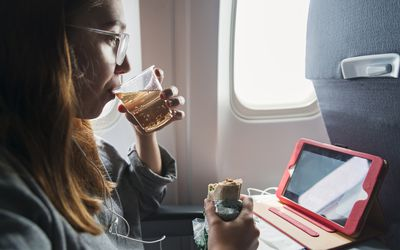 woman eating and drinking while seated on an airplane