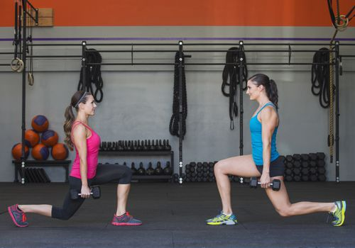 Two woman do lunges while holding dumbbells