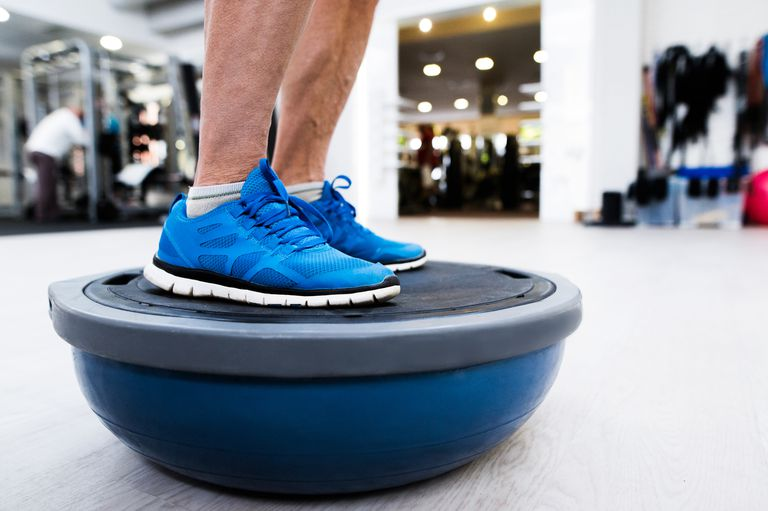 man standing on bosu ball