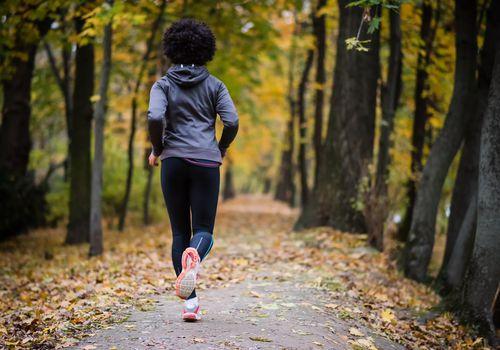 Mujer joven corriendo por el parque de otoño, tiro trasero.