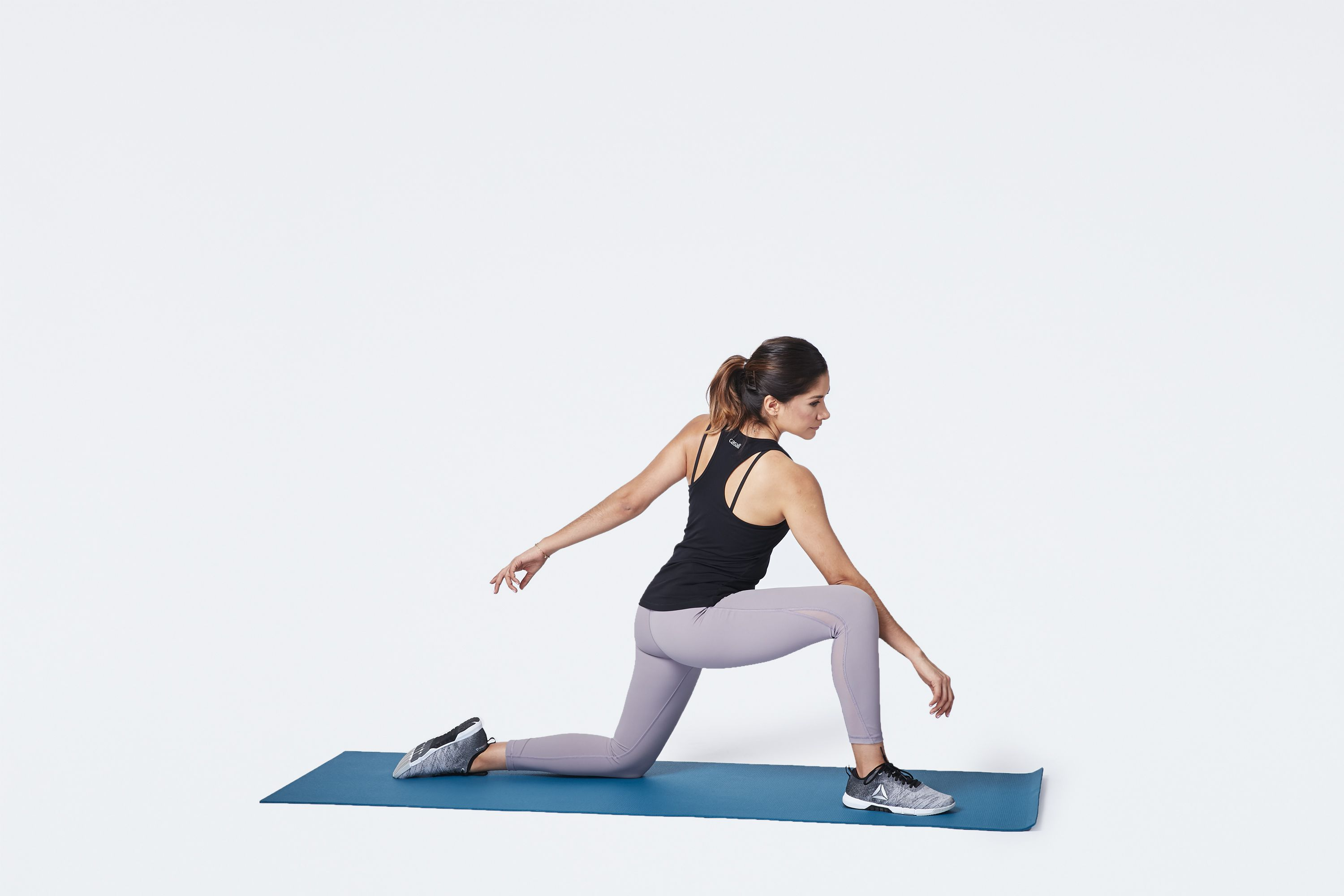 Woman performing low lunge twist stretch