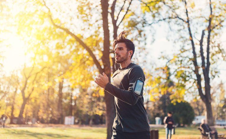 Sportsman jogging in the autumn park