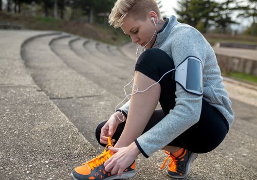 Young woman trail runner tying shoelaces on new running shoes