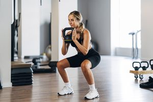 Young female athlete lifting Kettle bell while crouching in gym