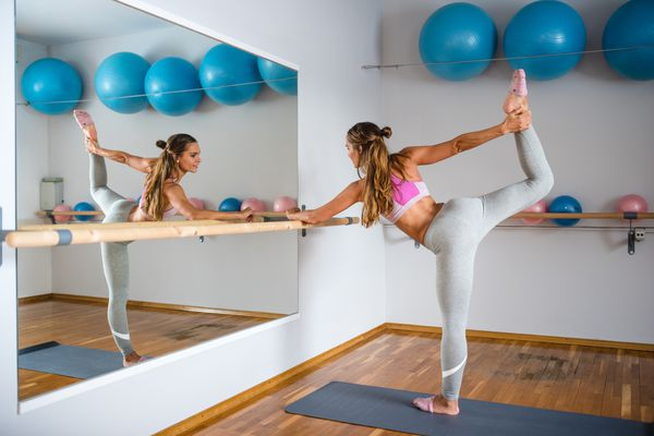 Woman stretching using a barre