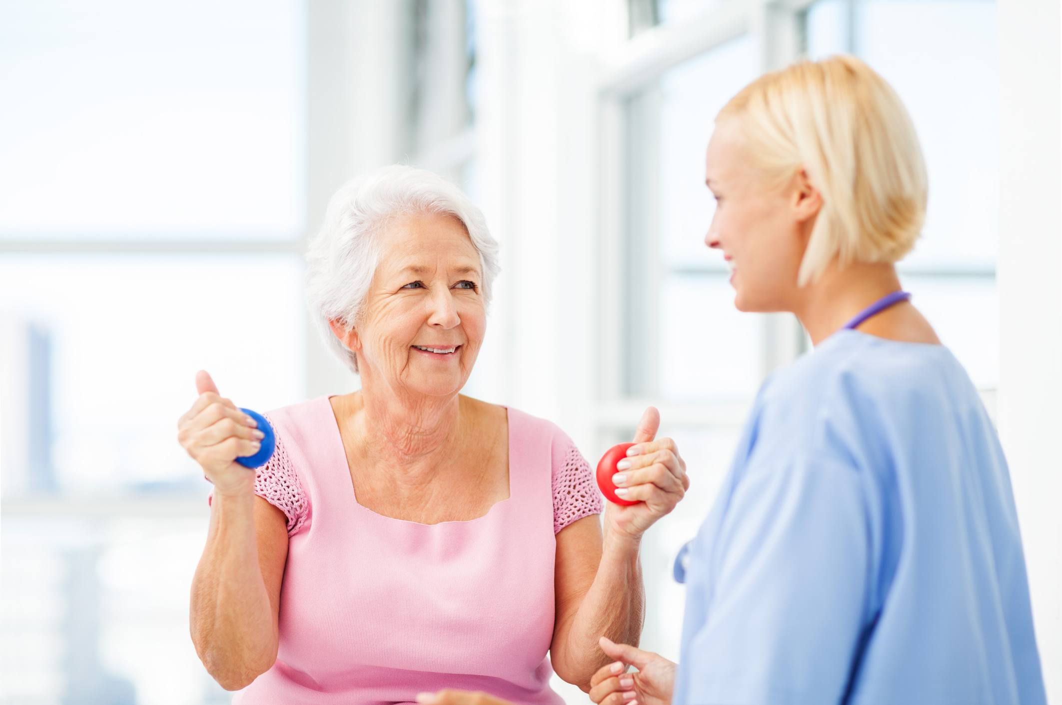 Nurse and senior patient with hand therapy balls