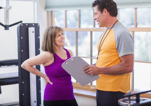 Caucasian woman working with personal trainer in gym