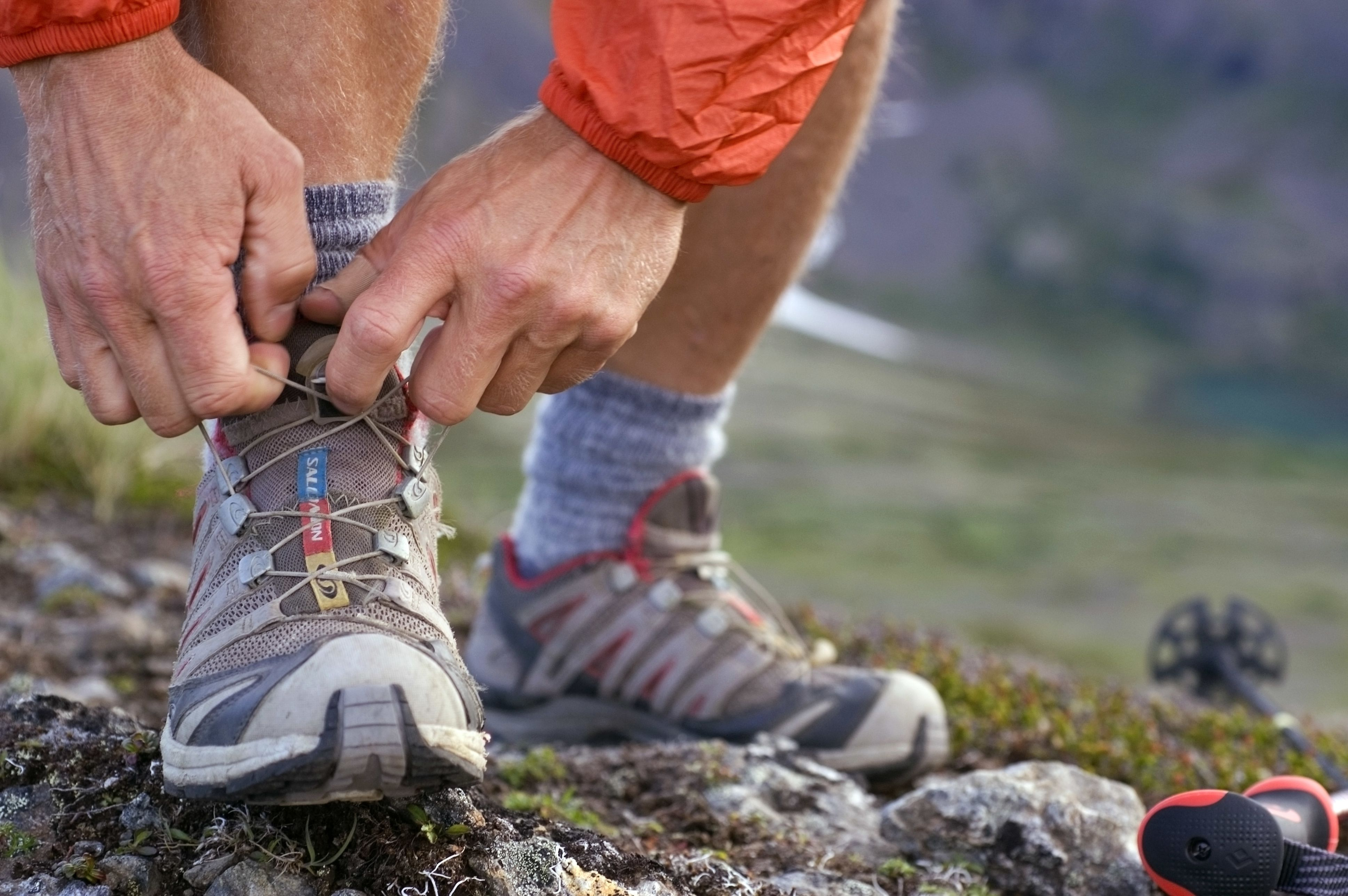 Close up of running shoes as man checks ties during run through the Chugach Mountains on Chugach front range peaks Southcentral Alaska summer
