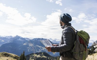 Austria, Tyrol, young man with map in mountainscape