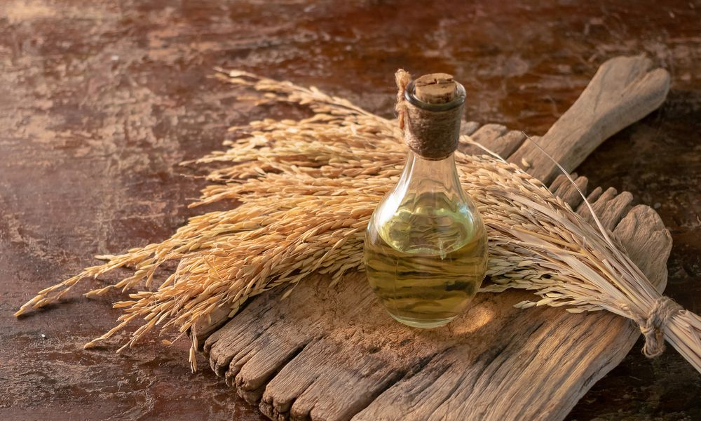 Bottle of rice bran oil and unmilled rice on wooden background