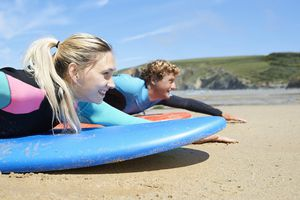 Man and woman practicing surfing on the beach