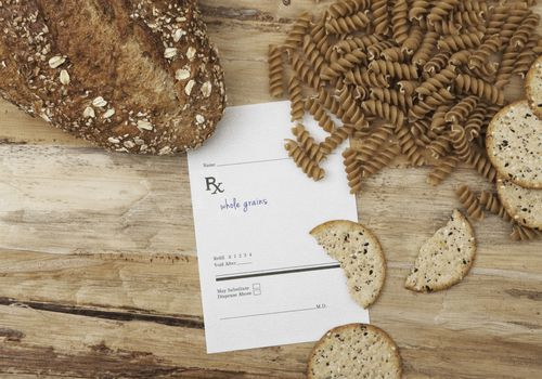 Pan integral, pasta y galletas saladas junto a una hoja de prescripción que dice